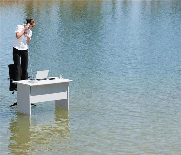 person standing at desk chair in the middle of flood waters