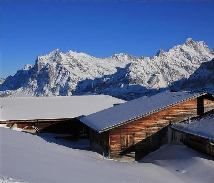 Snowcapped mountains and snow piled on rooftop of home