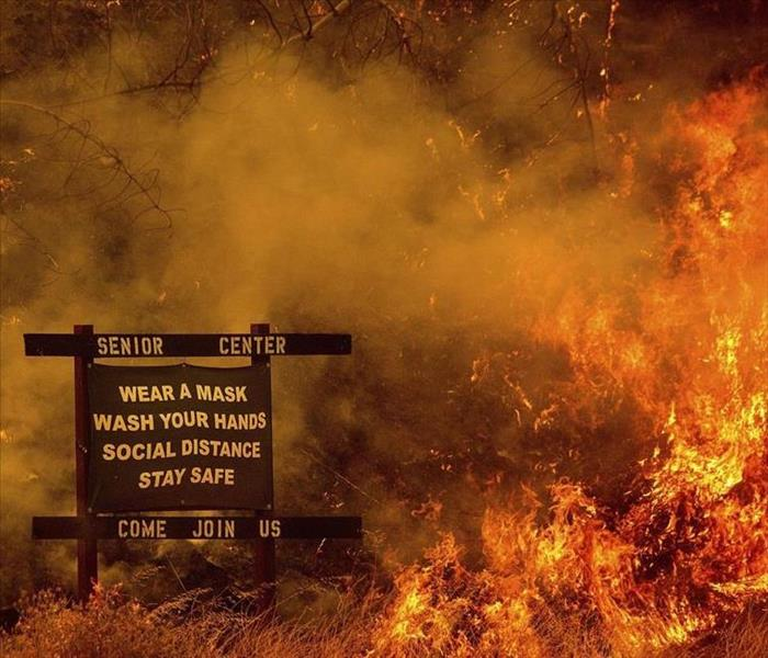 wildfire burning near street sign